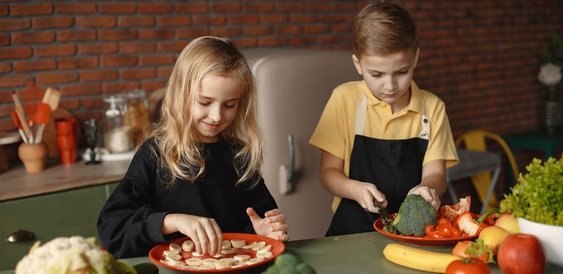 two healthy kids cutting vegetables