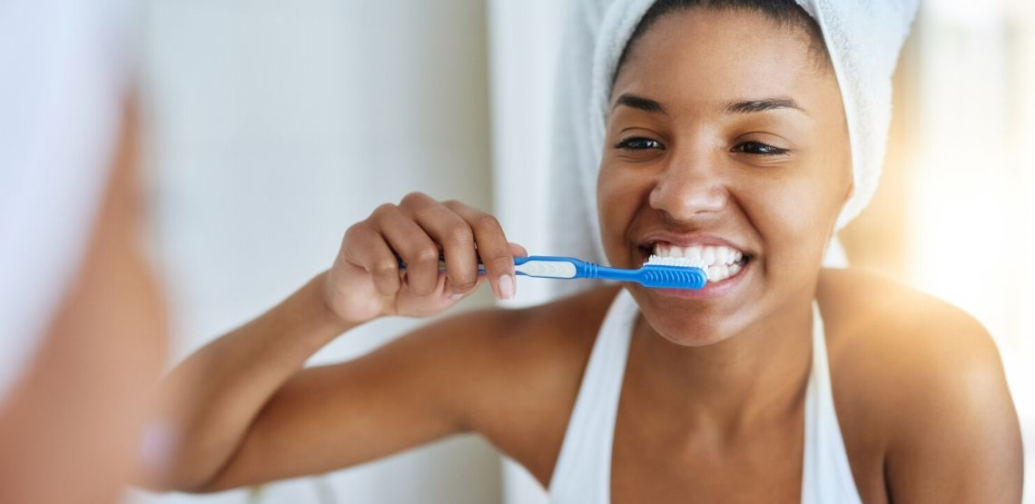 a woman brushing her teeth with whitening toothpaste