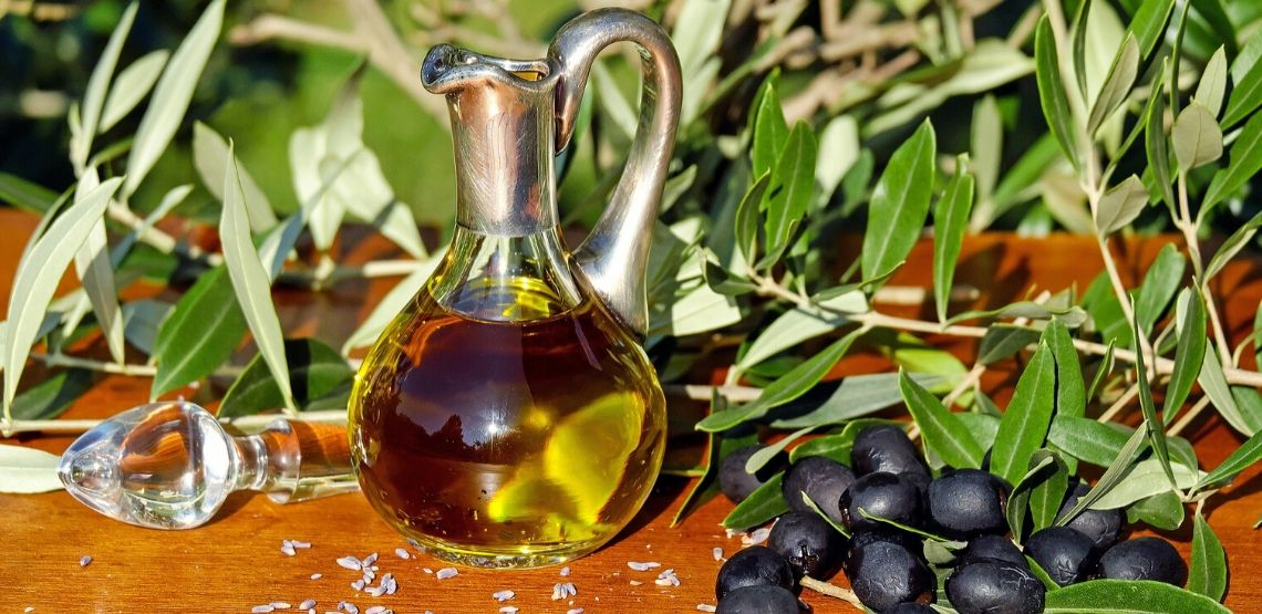 a bottle of olive oil beside an olive tree: an example of healthy fats