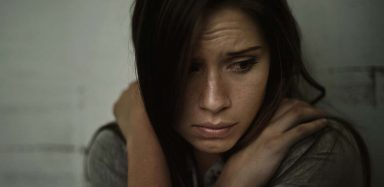 A girl looking sad and holding herself.