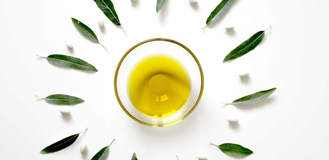 A bowl of olive oil on a white background.