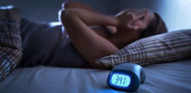 a woman with insomnia lying in bed, frustrated that she can't sleep