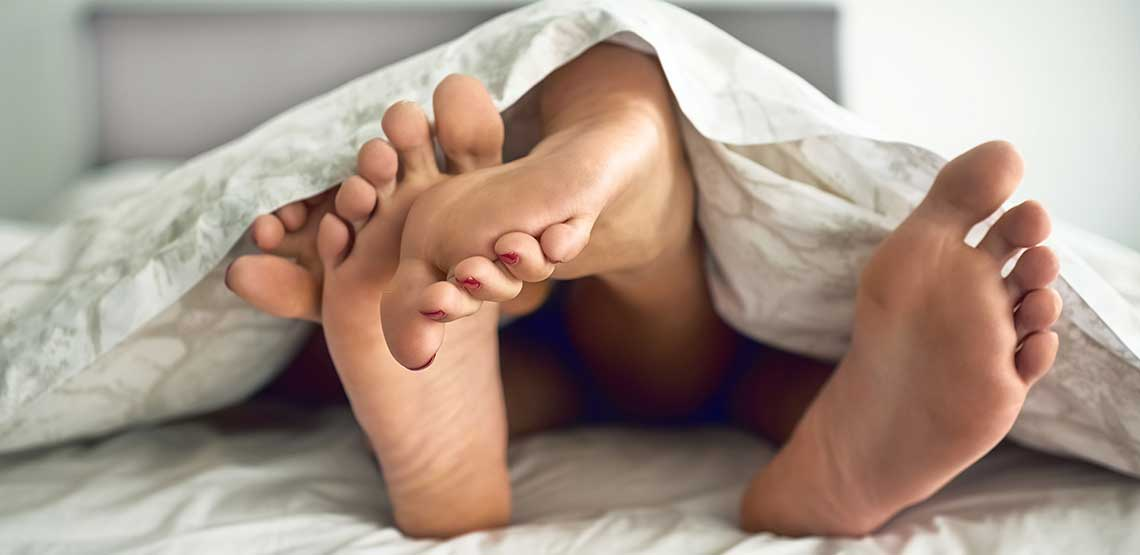 People's feet on top of each other, under bed covers