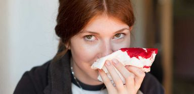a girl using a tissue to stop a nosebleed