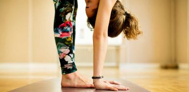 a woman doing Vinyasa yoga, an example of yoga for flexibility