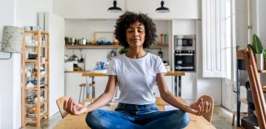 a woman sitting crossed legged on her kitchen table while meditating for mindfulness based stress reduction