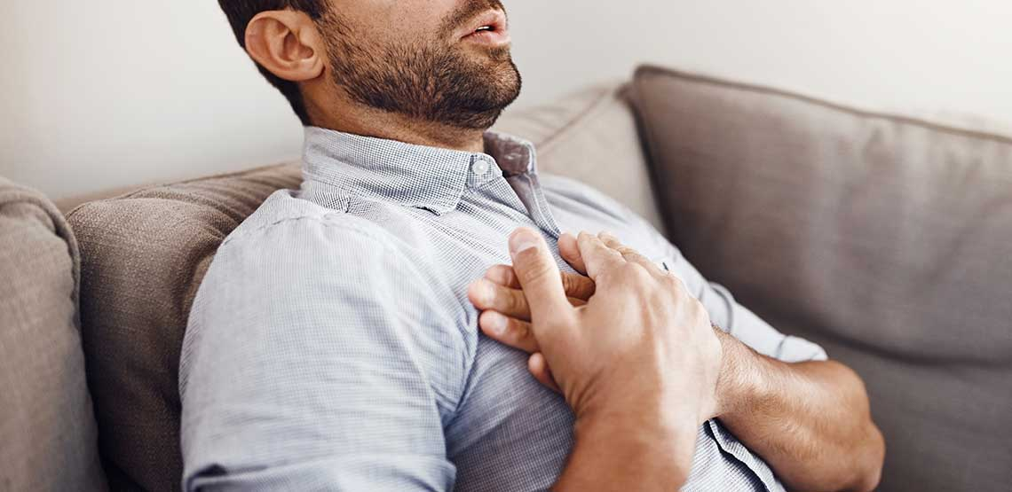 a man holding his chest, experiencing discomfort from heartburn