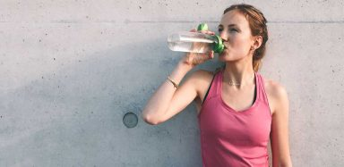 an active woman drinking water to prevent dehydration
