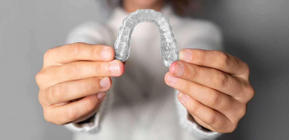 hands holding a clear teeth aligner