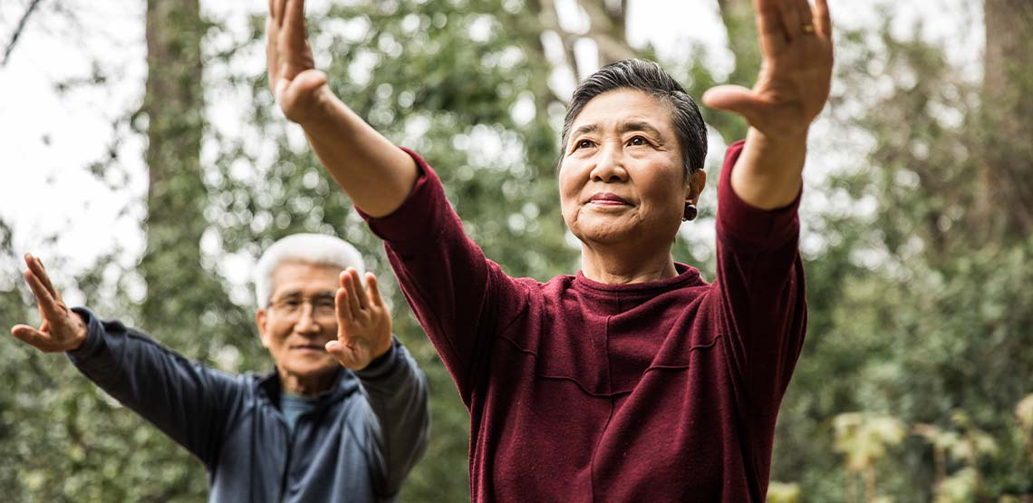 An elderly couple exercising outside.
