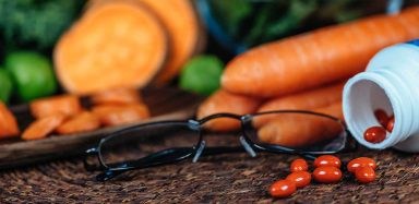 A pair of glasses next to vitamins and veggies.