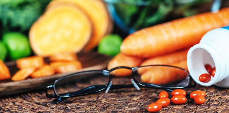 A pair of black glasses sitting next to vitamins and vegetables.