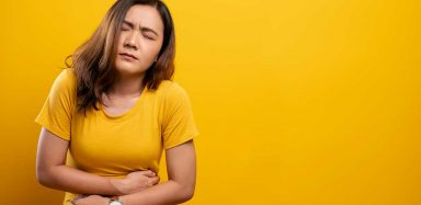 A woman in a yellow t-shirt holding her stomach, as if in pain.