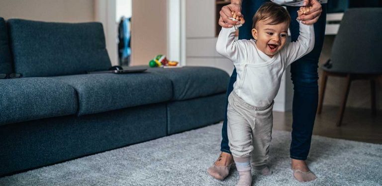 A toddler learning how to walk with its parent holding its hands