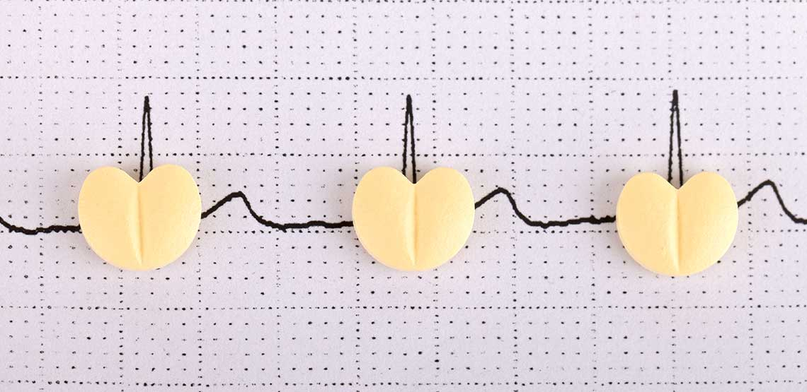 An electrocardiogram with pills on top of the paper.