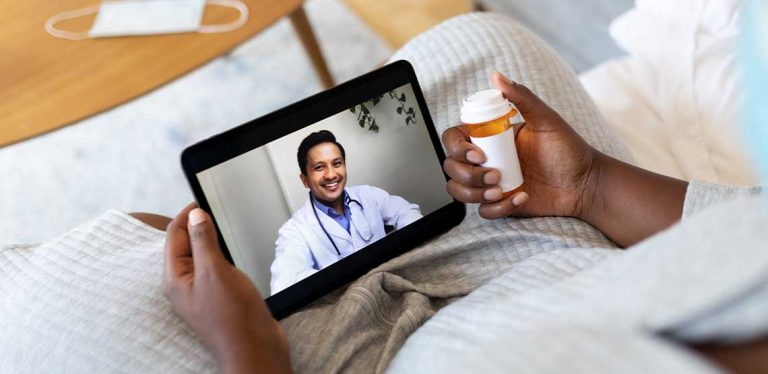 A person holding their tablet and medicine during a virtual doctor appointment on their tablet.