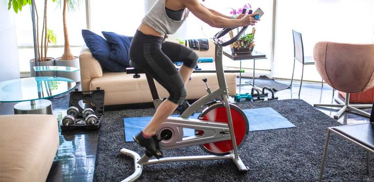 A woman riding on a bike trainer.