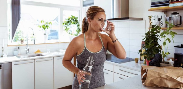 A woman standing in her kitchen drinking a glass of water