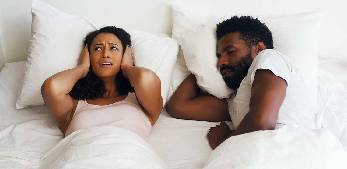A man snoring in bed while a woman puts a pillow over her ears.