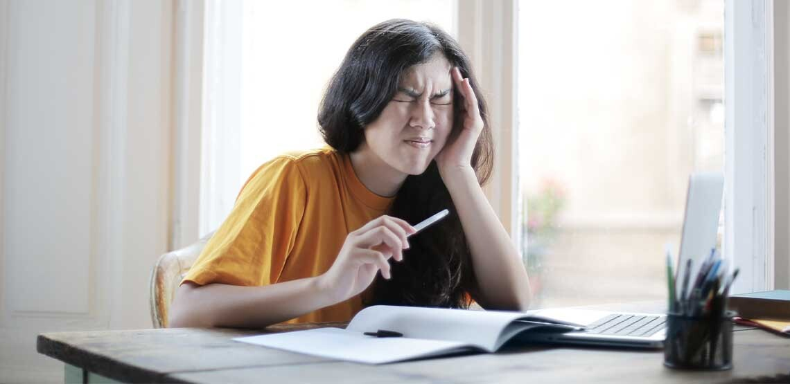 A women is sitting at her desk studying. She holds her head with her left hand and scrunches her face in pain.