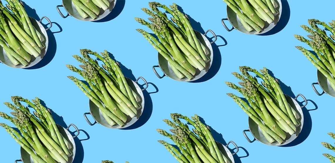 A repeating pattern of a colander full of asparagus on a blue background